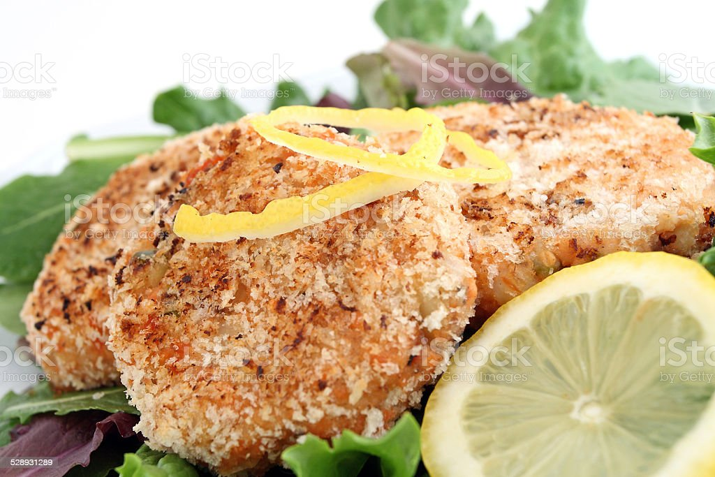 Healthy salmon cakes with lemon garnish stock photo