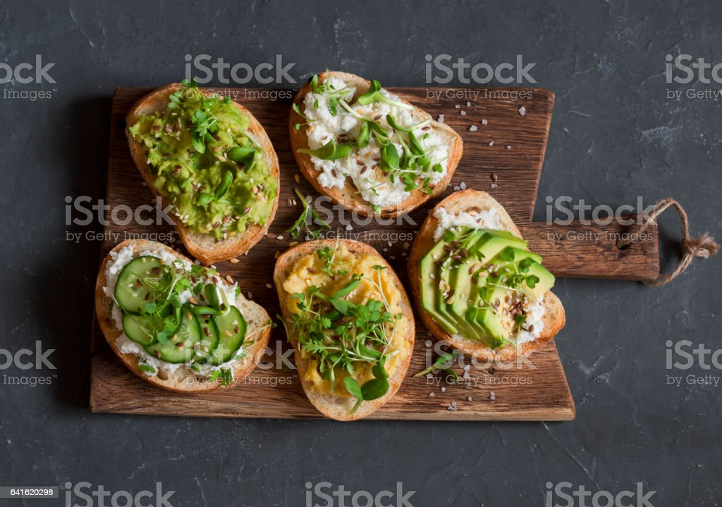 Healthy sandwiches with avocado, hummus, ricotta, cucumber, sunflower sprouts, micro greens and flax seeds. Healthy vegetarian snack stock photo