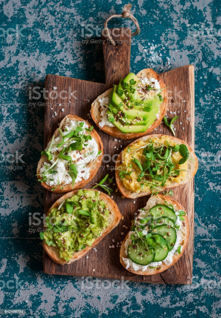 Healthy sandwiches with avocado, hummus, ricotta, cucumber, sunflower sprouts, micro greens and flax seeds. On a wooden cutting board, top view. Healthy vegetarian snack stock photo