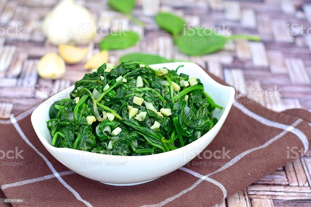 Healthy sautéed spinach with minced garlic stock photo
