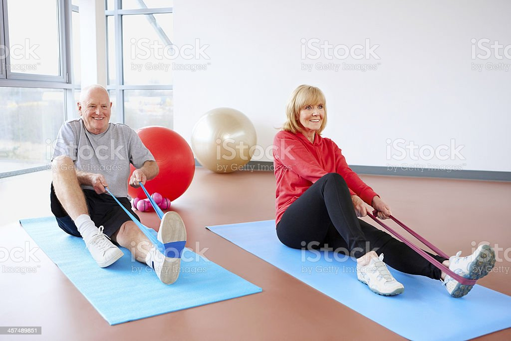 Healthy senior couple exercising with resistance bands stock photo