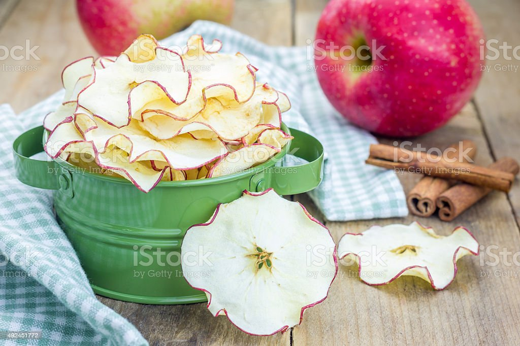 Healthy snack. Homemade apple chips on rustic wooden background stock photo