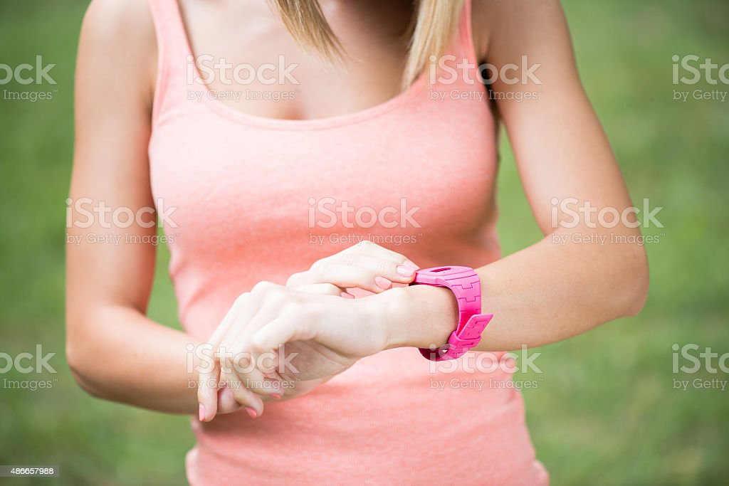 Healthy sport woman using smart watch to track fitness activity stock photo