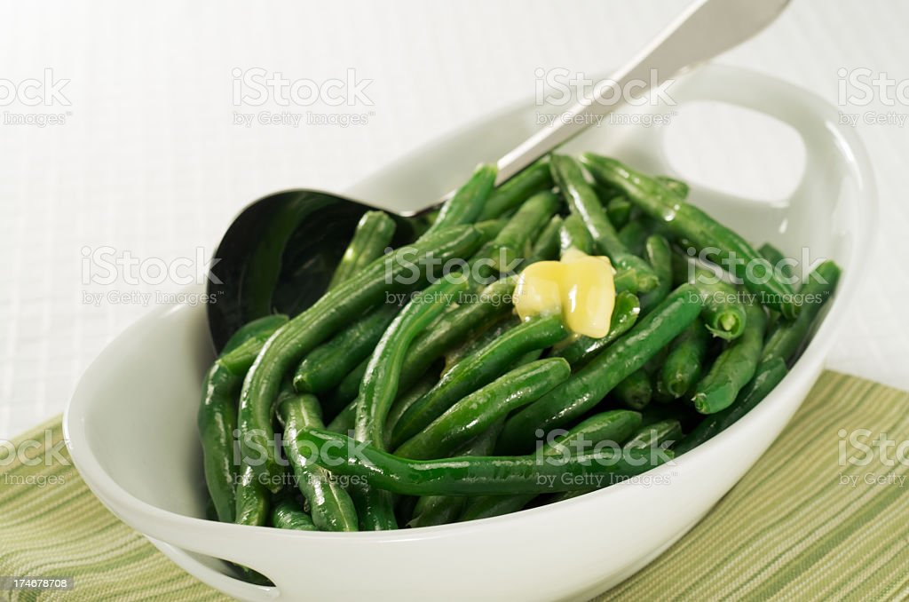 Healthy, steamed green beans with butter in a white bowl stock photo