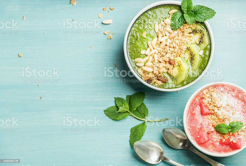 Healthy summer breakfast concept. Colorful fruit smoothie bowls on turquoise stock photo
