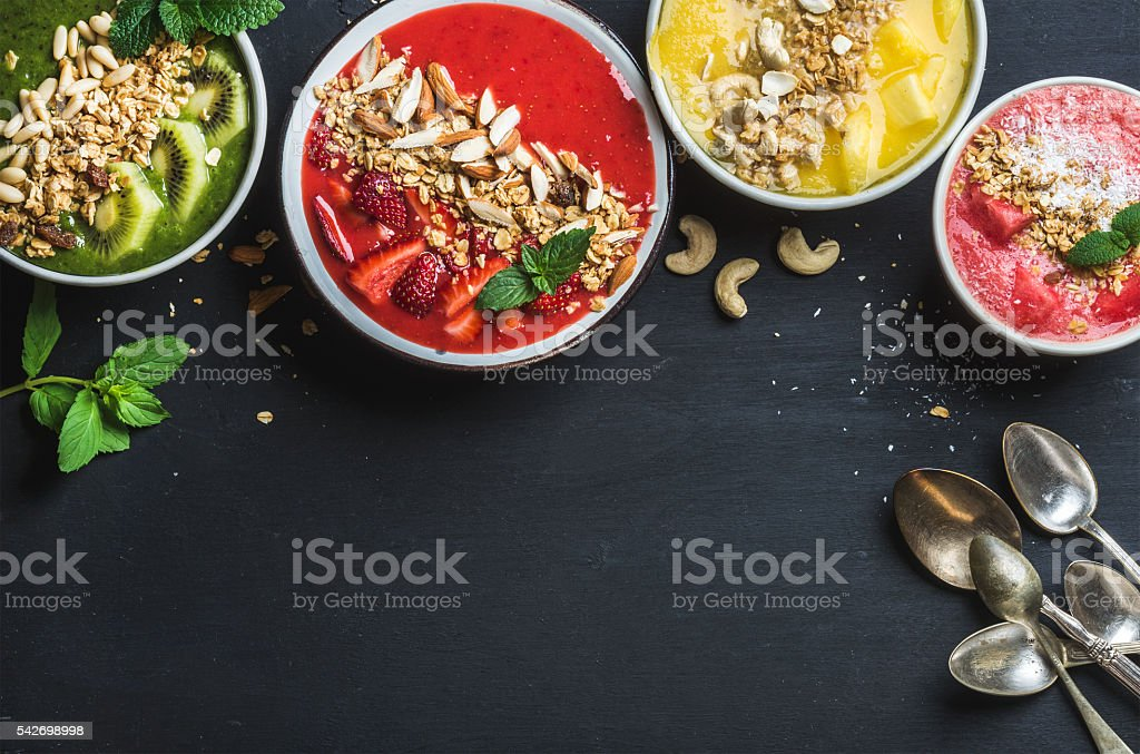 Healthy summer breakfast concept. Colorful fruit smoothie bowls with nuts stock photo