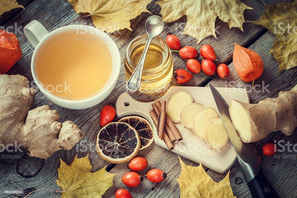 Healthy tea, honey, ginger root, dried lemon slice and cinnamon stock photo