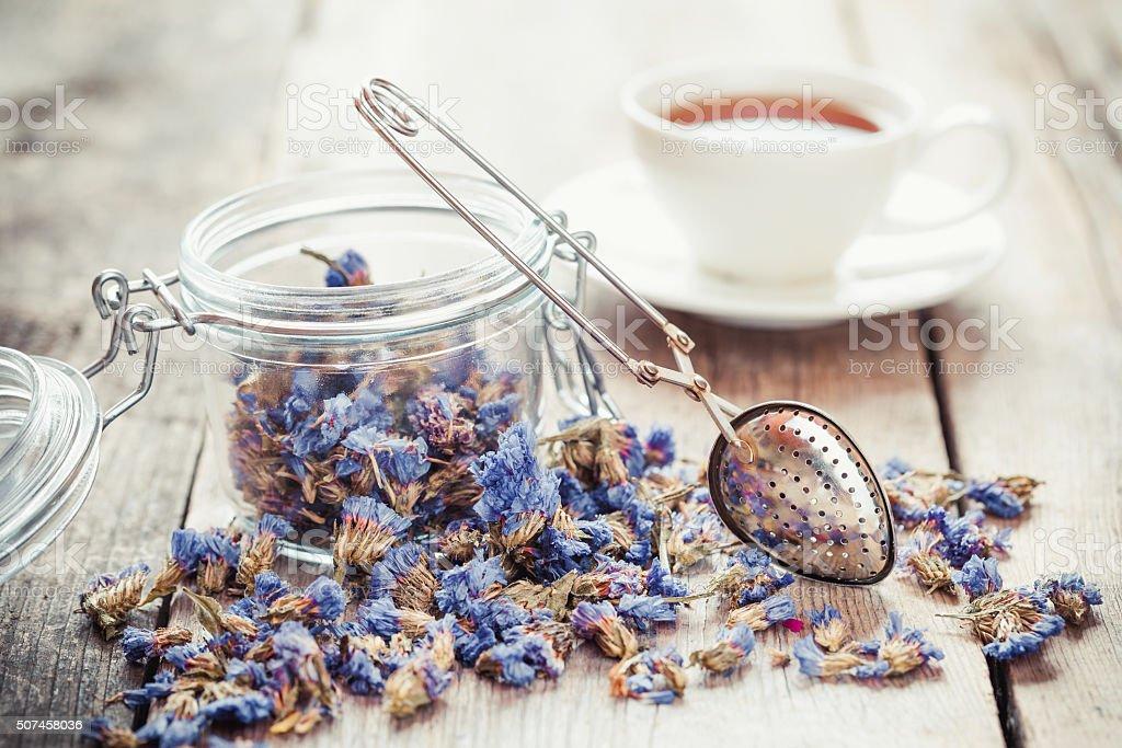 Healthy tea in jar, strainer and tea cup stock photo