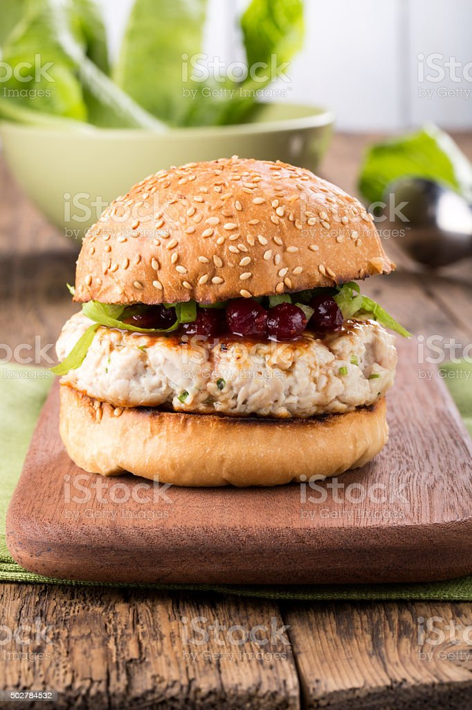 Healthy turkey burger on a bun with cranberry sauce stock photo