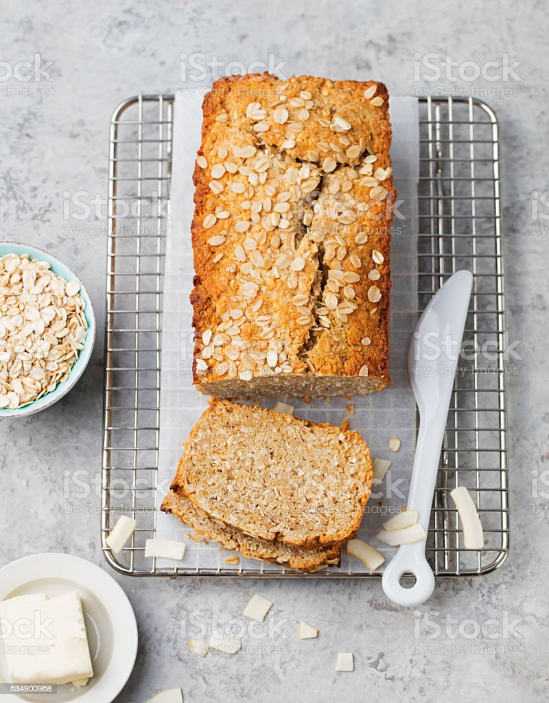 Healthy vegan oat, coconut loaf bread, cake on cooling rack stock photo