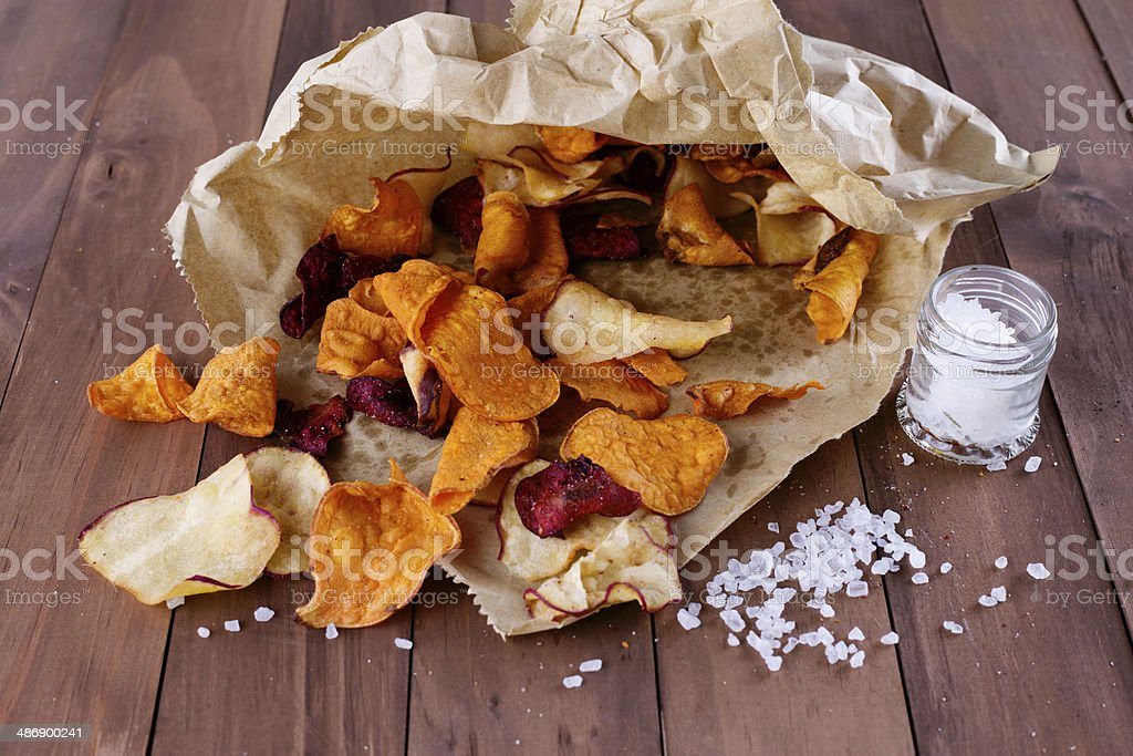 Healthy vegetable chips in a paper wrap with sea salt royalty-free stock photo