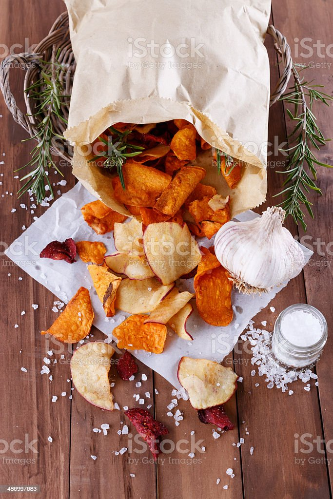 Healthy vegetable chips on paper with sea salt royalty-free stock photo