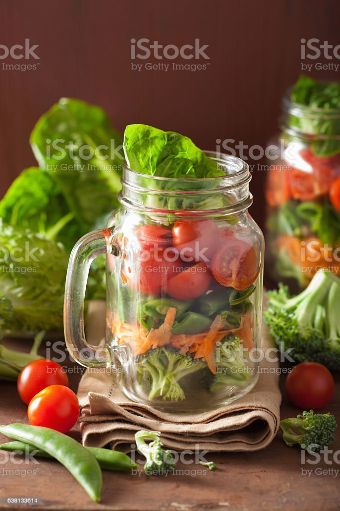 healthy vegetable salad in mason jar. tomato broccoli carrot pea stock photo
