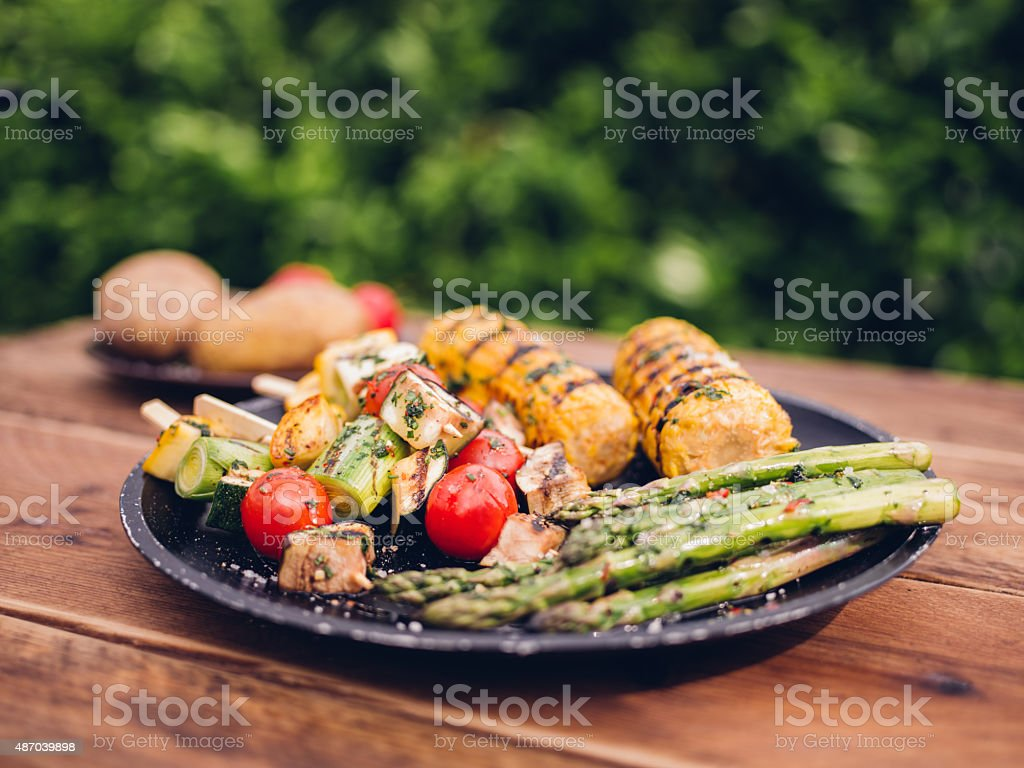 Healthy vegetables grilled and waiting on a wooden table outdoors stock photo