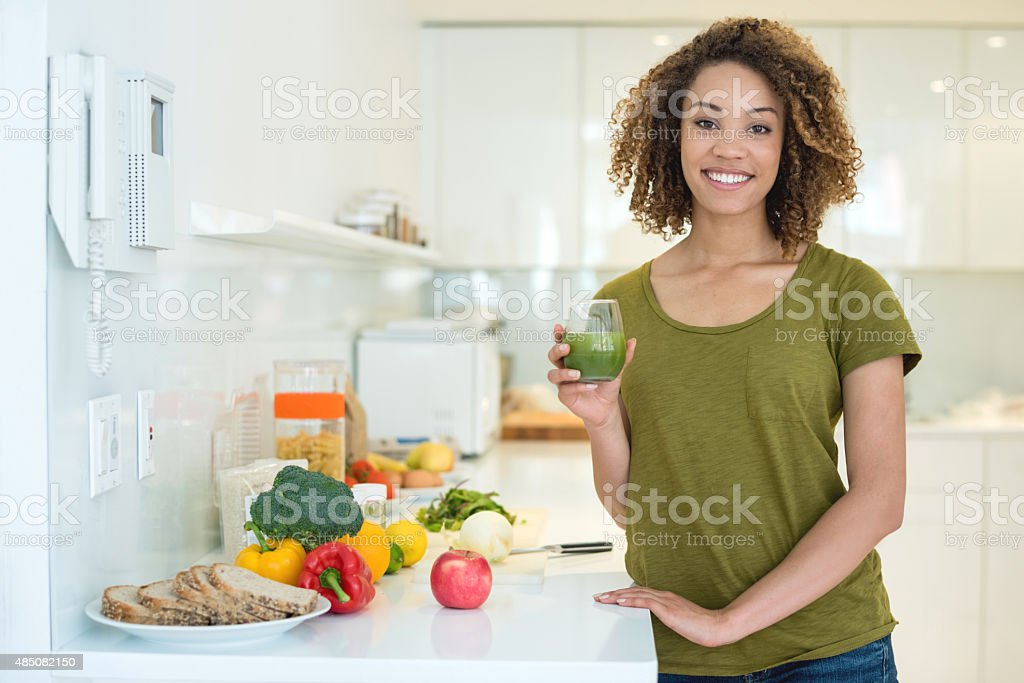 Healthy woman drinking a green juice stock photo
