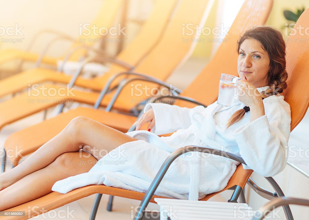 Healthy woman enjoys relaxing day at spa centre in bathrobe stock photo