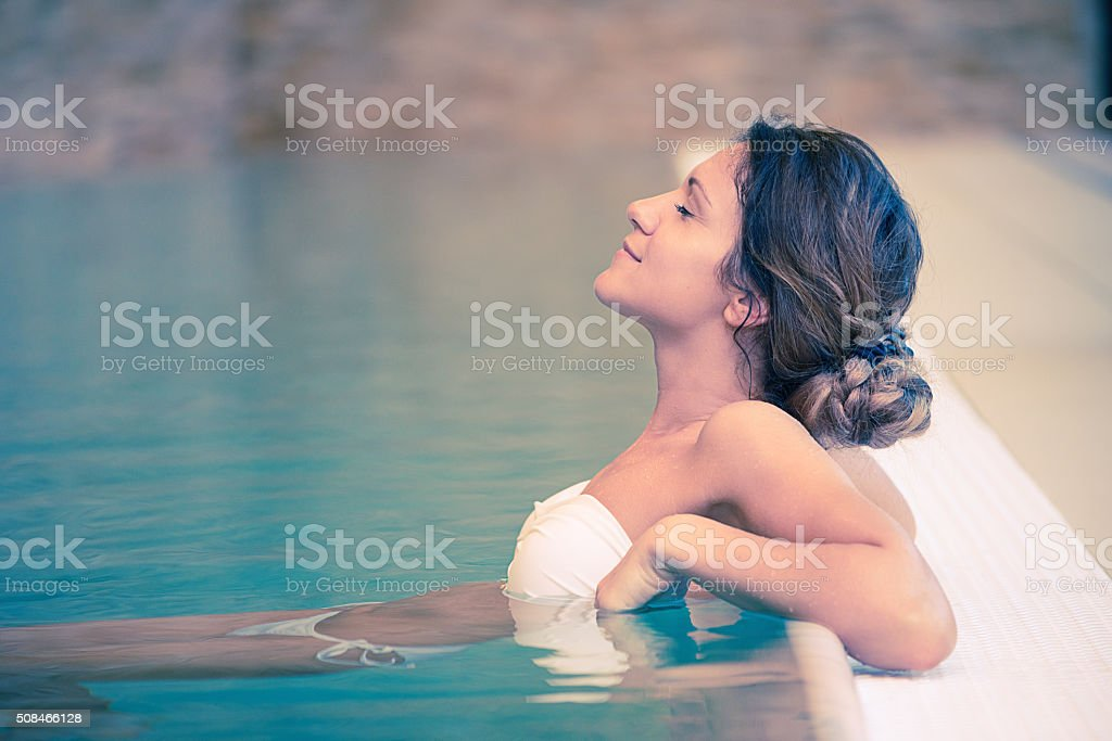 Healthy woman enjoys relaxing day at spa centre in swimsuit stock photo