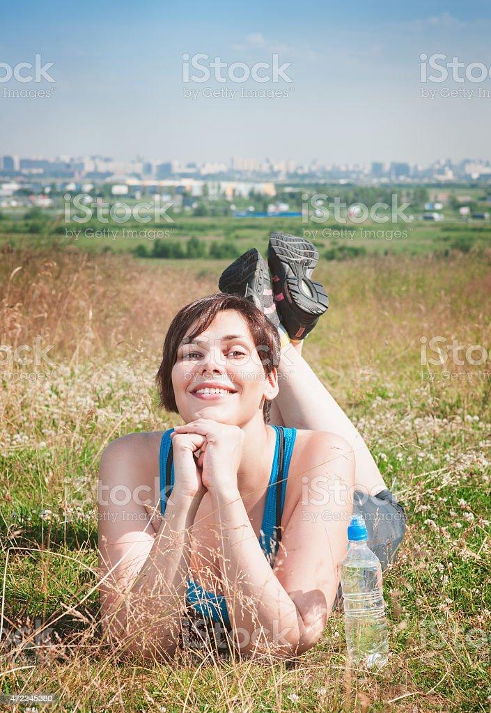 Healthy woman in sportswear lying on the meadow stock photo