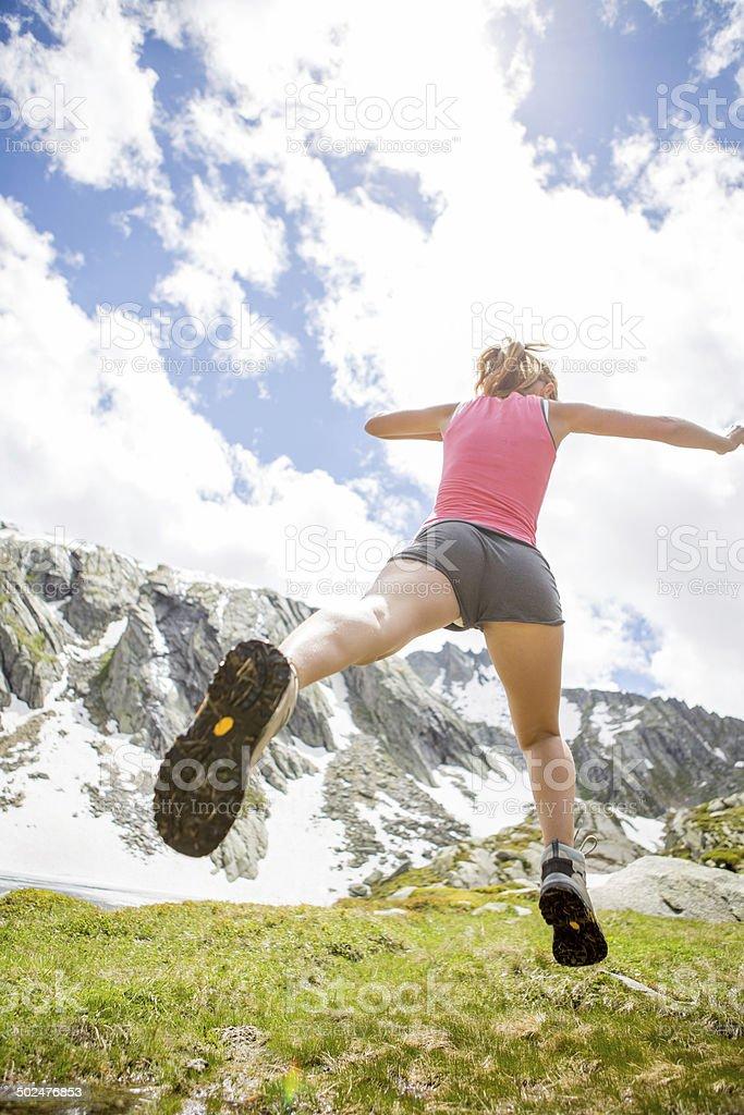 Healthy woman jumping through grass stock photo