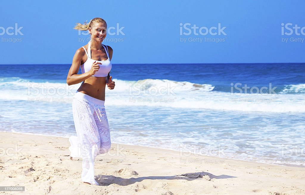 Healthy woman running on the beach royalty-free stock photo