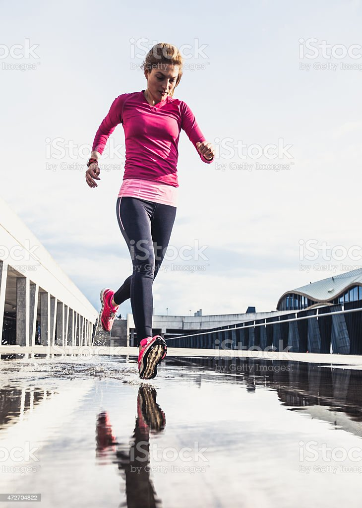 Healthy woman running on wet city street stock photo