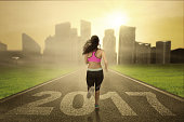 Healthy woman runs on road with 2017