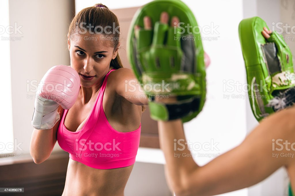 Healthy woman wearing boxing gloves, sparring with personal trainer stock photo