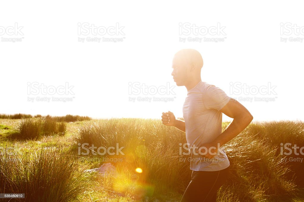 Healthy young african man running at the beach stock photo