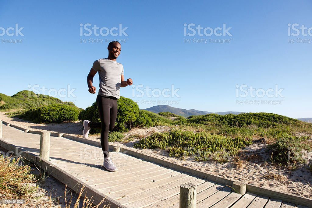 Healthy young african man running on path at the beach stock photo