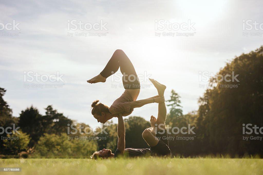 Healthy young couple doing acro yoga outdoors stock photo