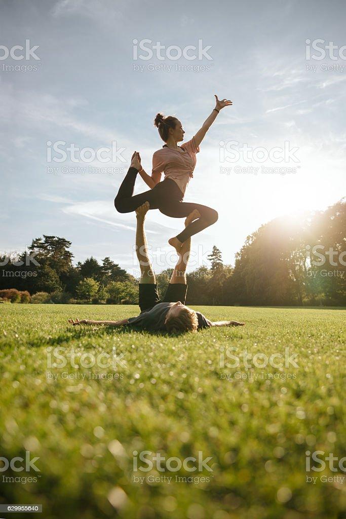 Healthy young couple doing acrobatic yoga stock photo