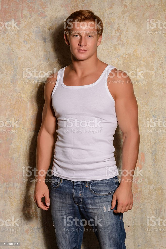 Healthy young guy posing near a wall. stock photo