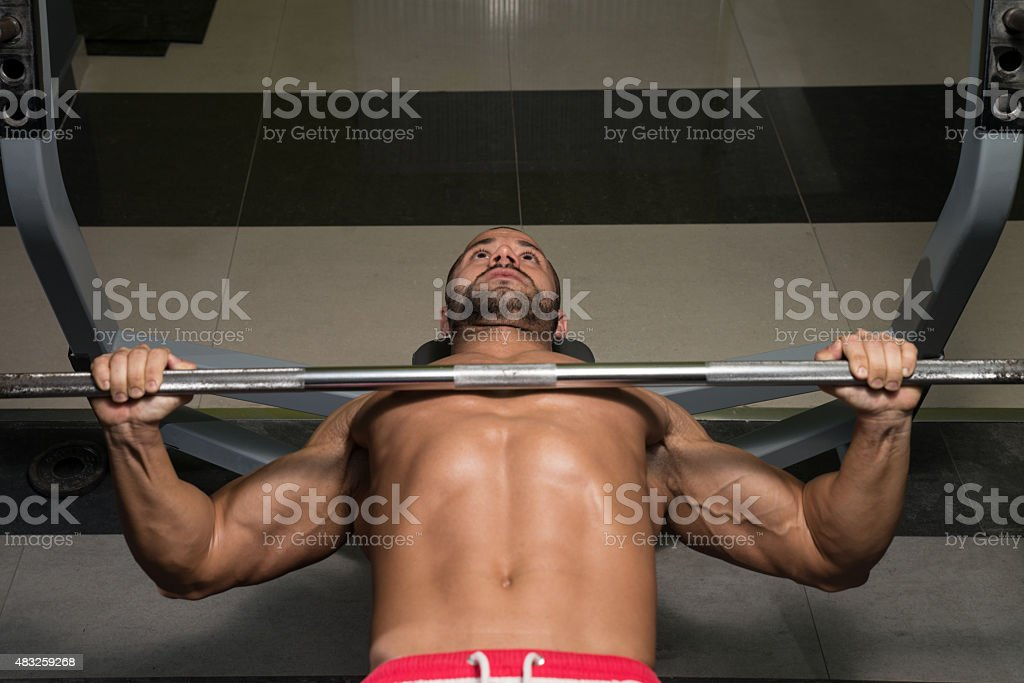 Healthy Young Man Doing Bench Press Exercise stock photo