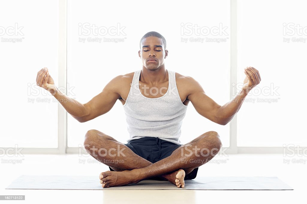 Healthy young man meditating on a yoga mat royalty-free stock photo