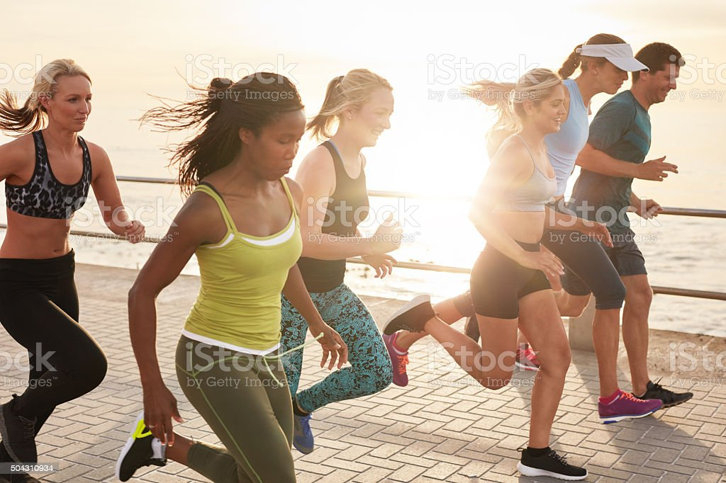 Healthy young people running race on seaside promenade stock photo