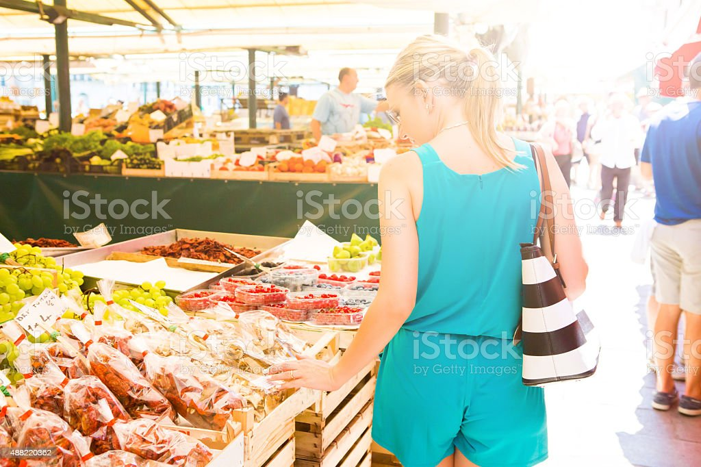 Healthy young woman shopping farmers market fresh fruits and vegetables stock photo