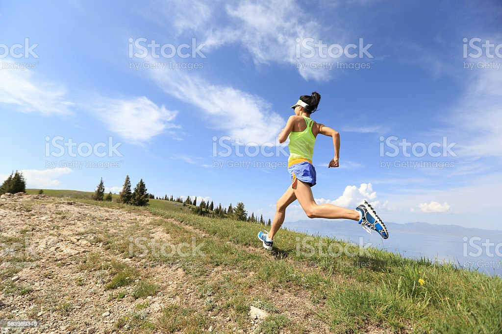 healthy young woman trail runner running on beautiful mountain peak stock photo