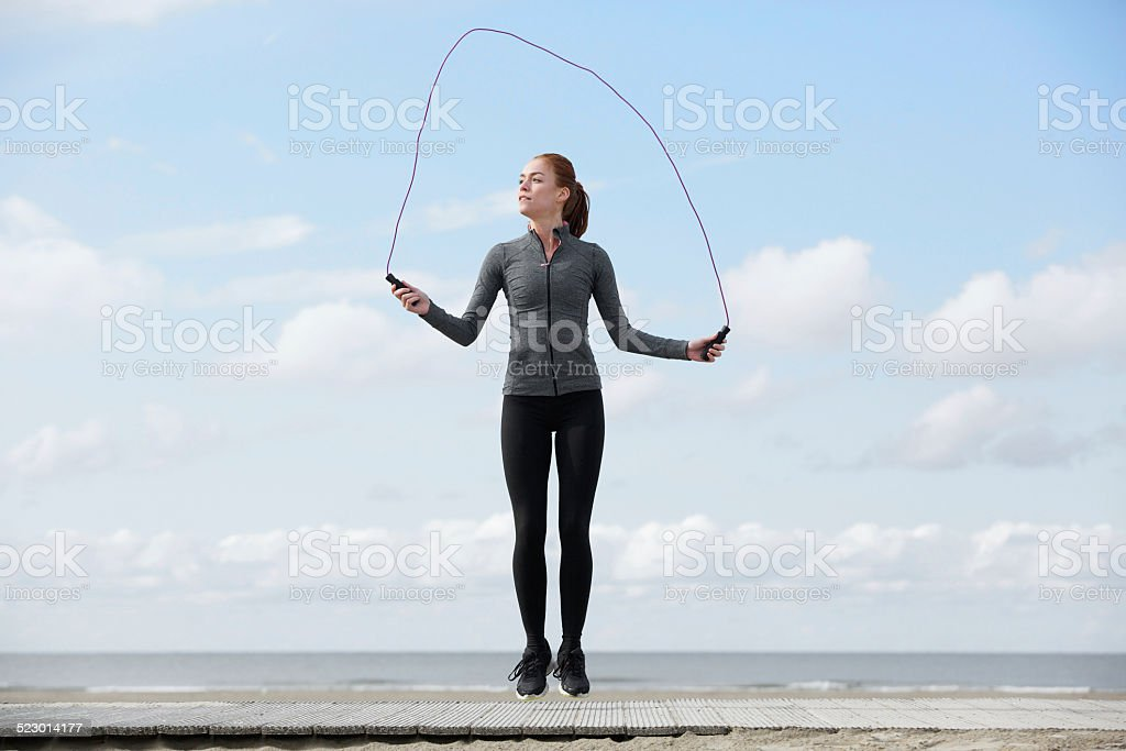 Healthy young woman with jump rope stock photo
