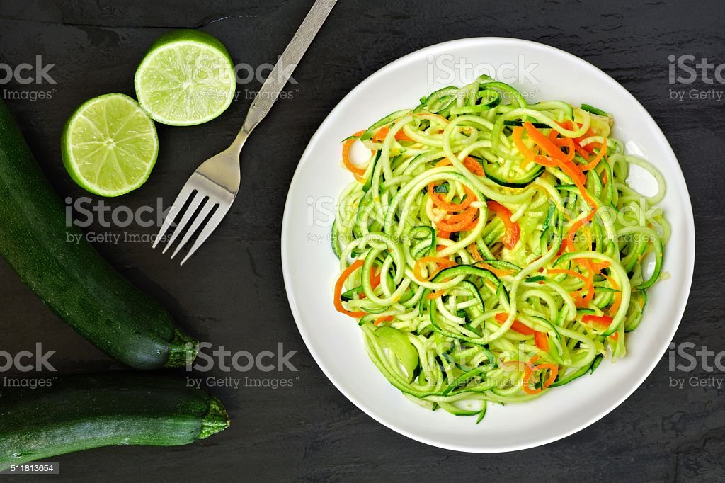 Healthy zucchini noodle dish with carrots and lime stock photo