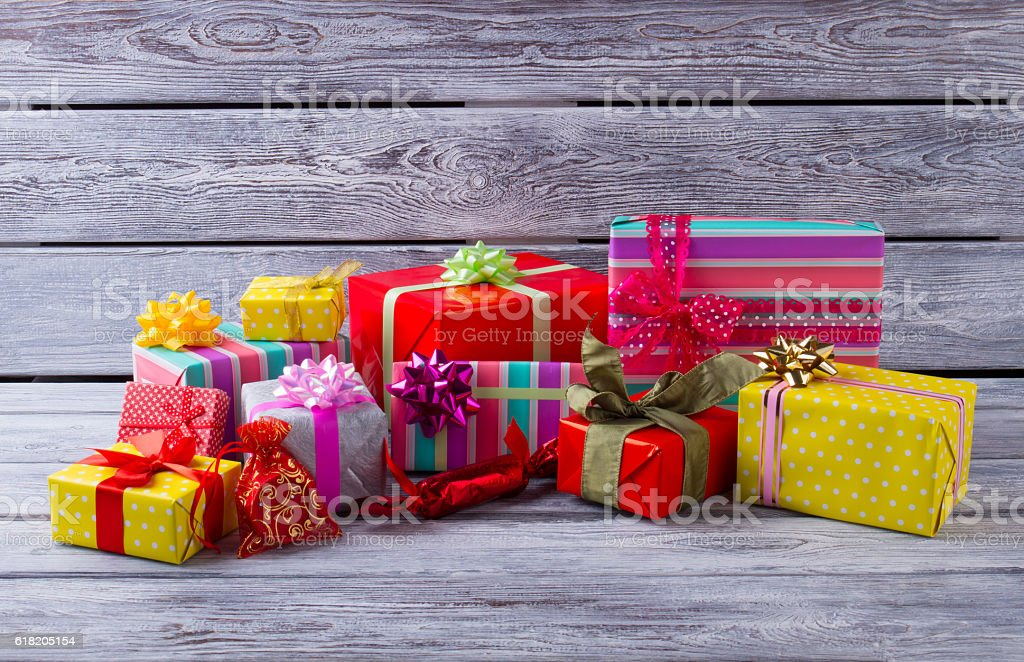 Heap of beautiful Christmas gifts on gray wooden background. stock photo