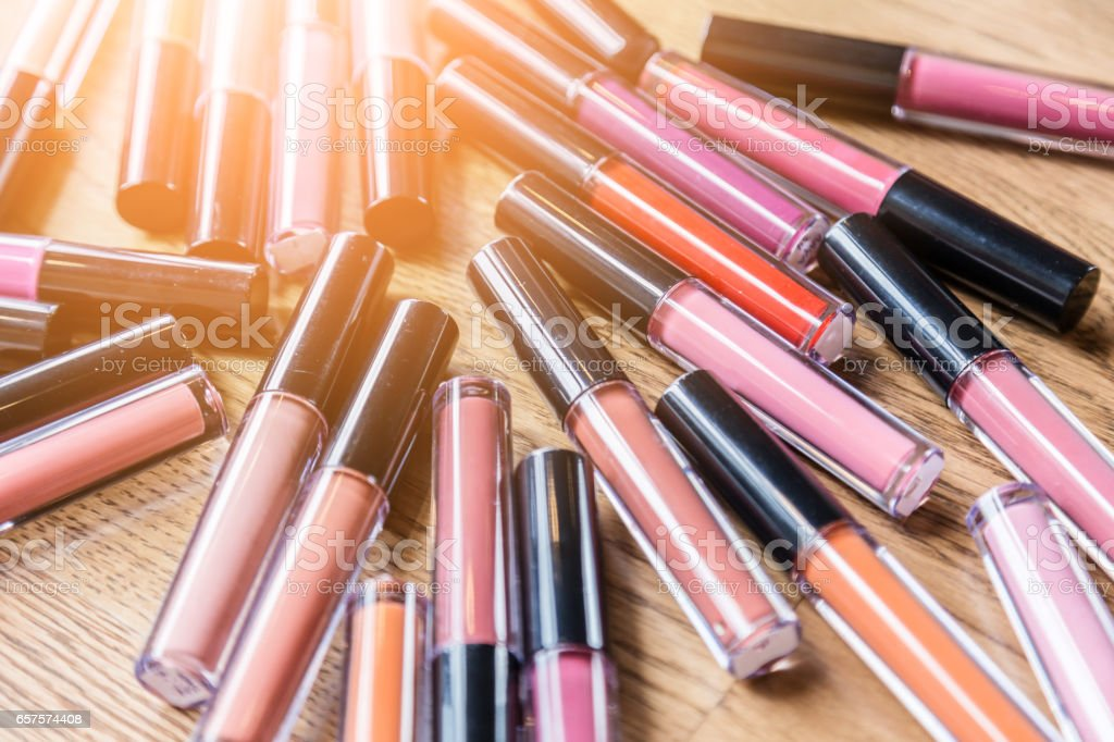 heap of bottle liquip lipstick on wooden table stock photo