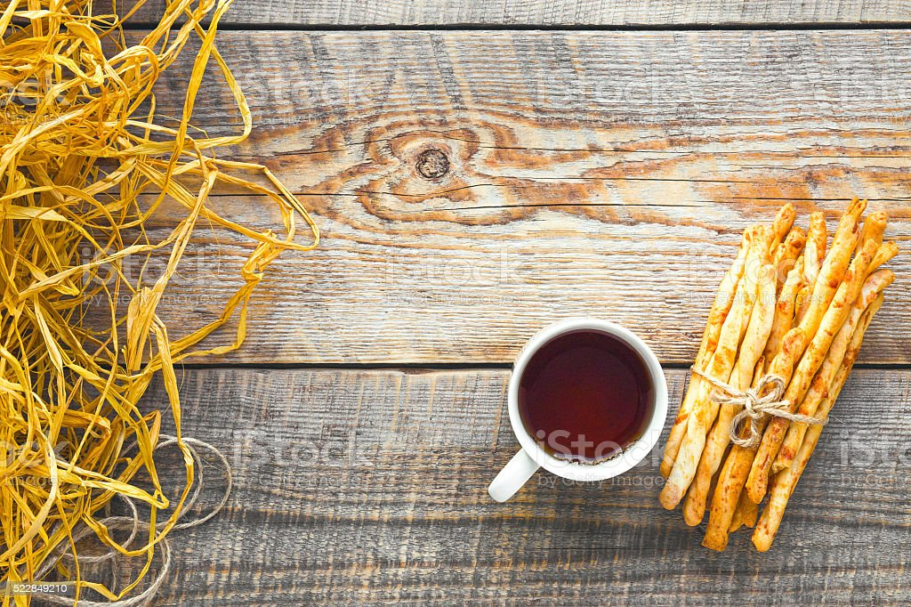 Heap of bread sticks with tea on wooden table stock photo