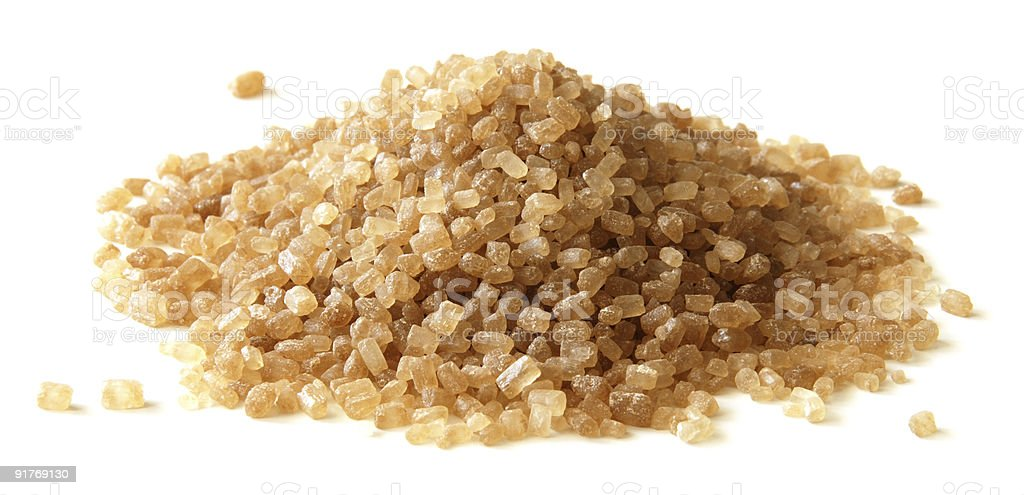 Heap of brown cane sugar crystals isolated on white stock photo