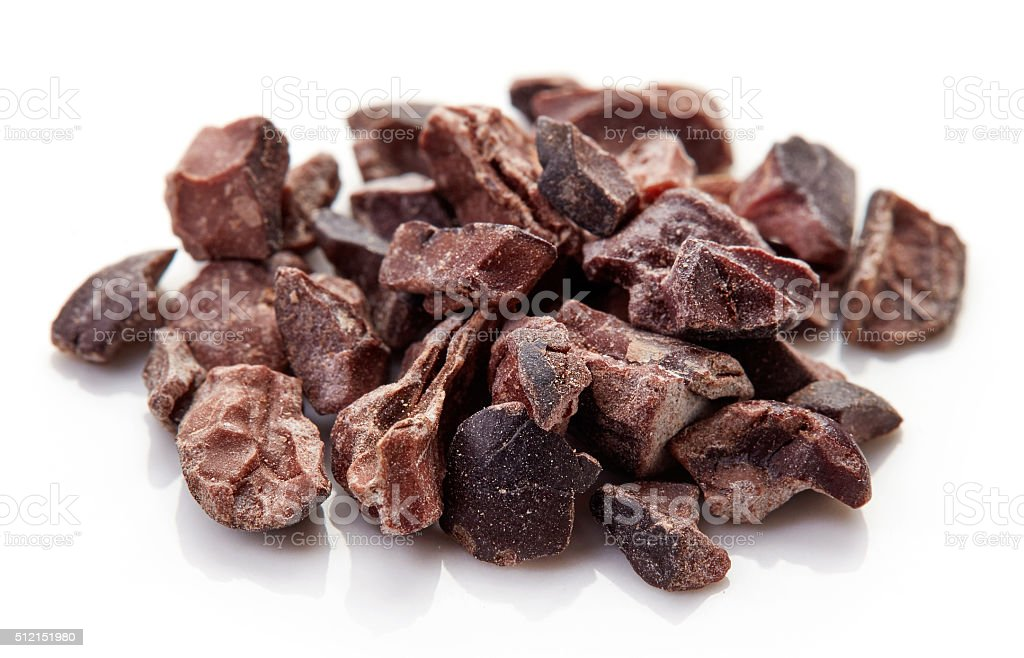 Heap of cacao nibs on white background stock photo