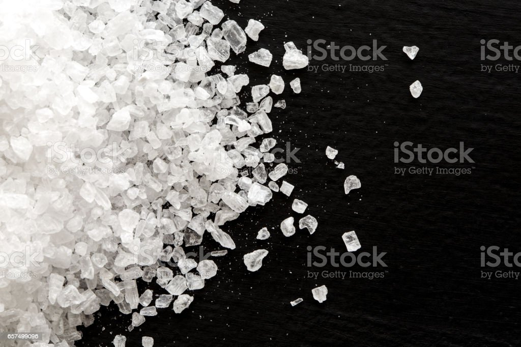 Heap of coarse salt on black from above. stock photo