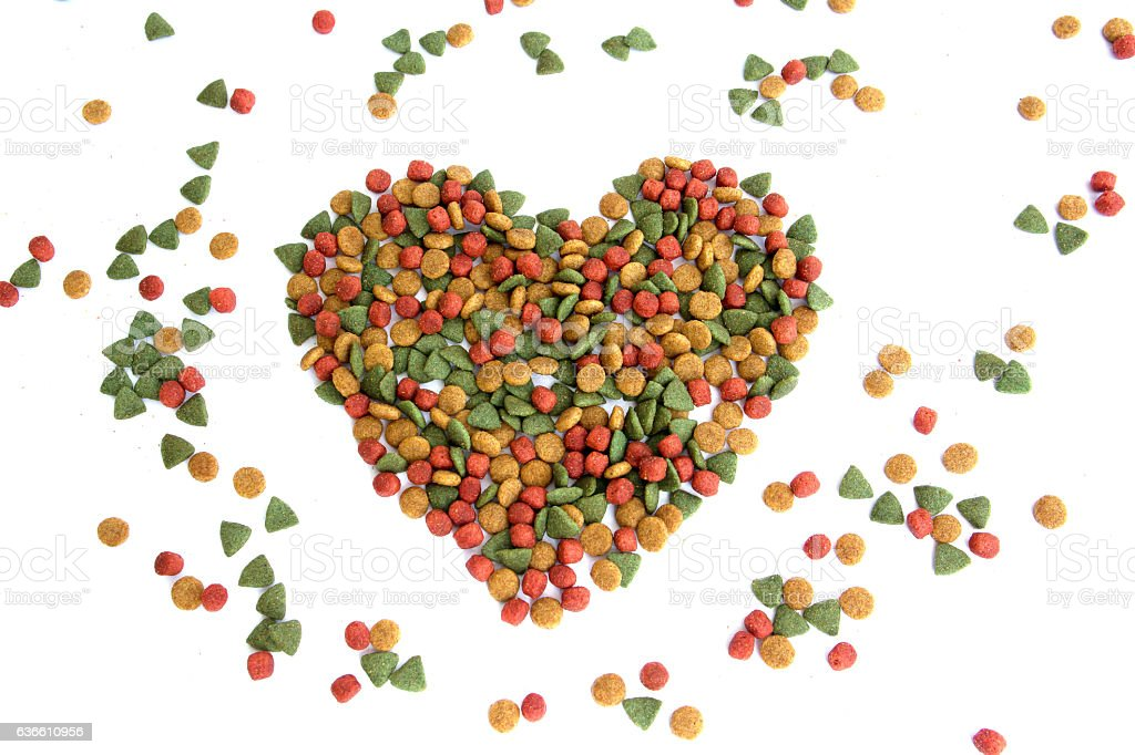 Heap of colorful dried dog food in a heart shape stock photo