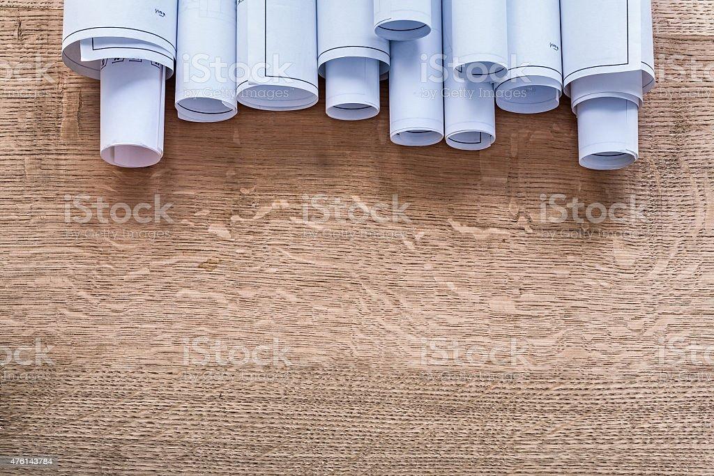 Heap of construction plans on wooden oaken board maintenance con stock photo