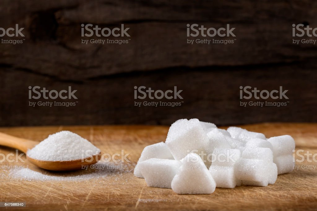 Heap of different sugar cubes shapes and wooden spoon filled with sugar stock photo