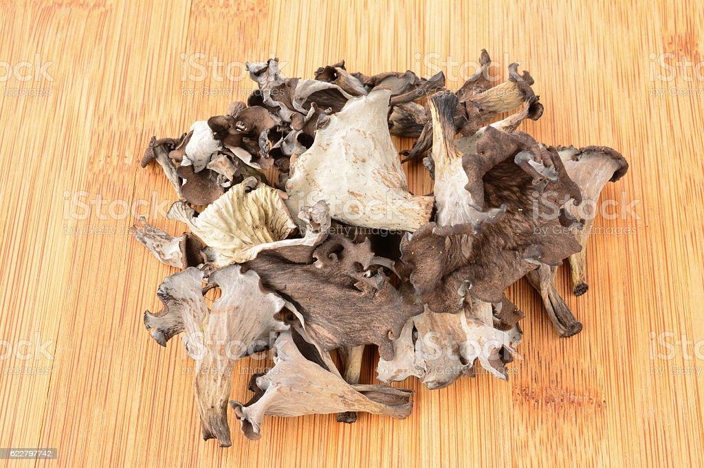 Heap of dried Horn of Plenty mushrooms on bamboo stock photo