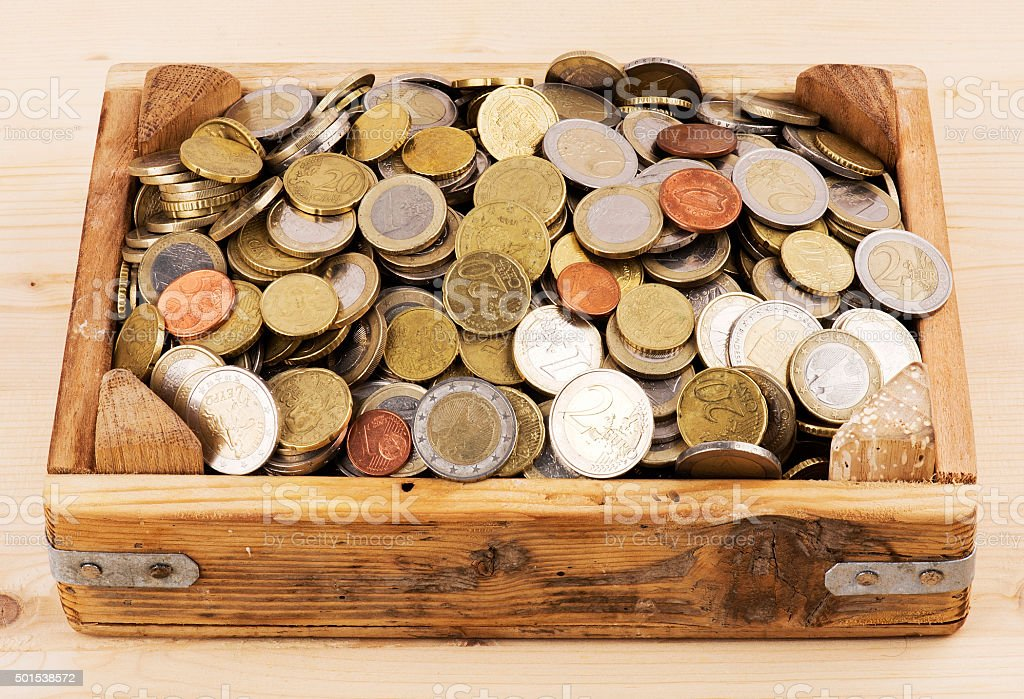 Heap of Euro Coins in Wood Container stock photo